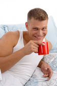Smiling male drinking coffee in bed — Stock Photo
