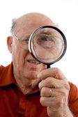 Old man looking through lens — Stock Photo
