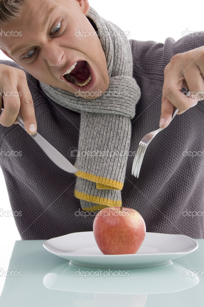 Young man going to eat apple with fork and knife on an isolated background — Stock Photo #1655029