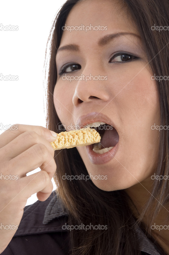 Pretty woman eating cookies on an isolated background  Stock Photo #1658608