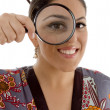 Emale watching through magnifying lens — Stock Photo