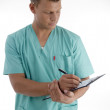 Young male doctor writing prescription — Stock Photo