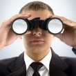 Young businessman using binoculars — Stock Photo