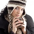 Woman with winter cap holding coffee mug — ストック写真