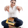 Young female with books pointing — Stock Photo