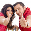Cheerful young couple showing thumbs up — Stock Photo