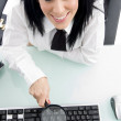 Female with magnifier on keyboard — Stock Photo