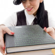 Student in cap holding stack of books — Stock Photo