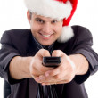 Man in christmas hat with remote control — Stock Photo