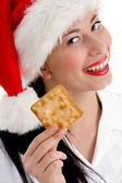 Woman with christmas hat holding biscuit — Stock Photo
