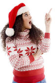 Young woman in christmas hat indicating — Stock Photo