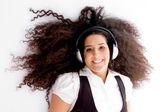 Mooie vrouw genieten van muziek op verdieping — Stockfoto
