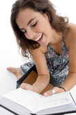 Smiling young student reading book — Stock Photo