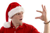 Young santa looking at his palm — Stock Photo