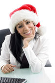 Female wearing christmas hat at work — Стоковое фото