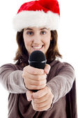 Young female in santa hat holding mic — Stock Photo