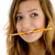 Beautiful girl holding pencil in mouth — Stock Photo