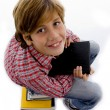 Boy sitting on pile of books — Stock Photo