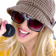 Glamorous woman singing into mic - Stock Photo