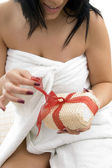 Woman in towel unwrapping new scrubber — Stock Photo