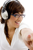Smiling woman pointing with headphones — Stock Photo