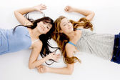 Young sisters lying on floor, posing — Stock Photo