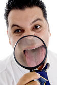 Businessman with magnified tongue — Stock Photo