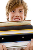Front view of smiling boy holding books — Stock Photo