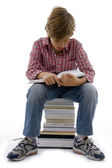 Front view of boy sitting on books — Stock Photo