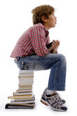 Young boy sitting on stack of books — Stock Photo