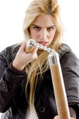 Aggressive female holding nunchaku — Stock Photo