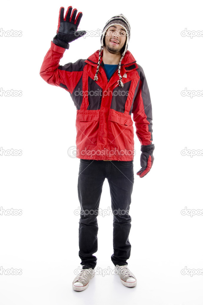 Man wearing winter cap and jacket waving hello against white background — Stock Photo #1670083
