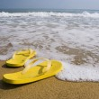 Beach slippers on a sandy beach, summer - Stok fotoğraf
