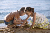 Boy and girl playing in sand — Stockfoto
