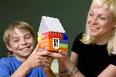 Woman and boy hold a toy house — Stock Photo