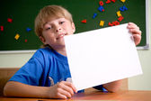 Boy holding up white sheet of paper — Stok fotoğraf