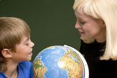Boy and young woman look at globe — Stock Photo