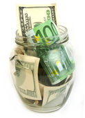 Dollar and euro bills in glass jar — Stock Photo