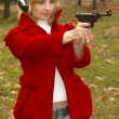 Girl in headphones with pistol — Stock Photo