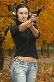 Girl in headphones with pistol — Stock Photo