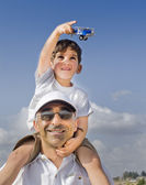 Boy on shoulders with toy airplane — Stock Photo