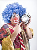 Unhappy clown with alam clock — Stock Photo