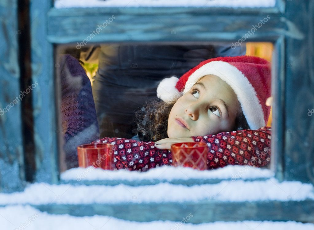 Little girl with a Santa hat  looking outside  Stock Photo #1336060