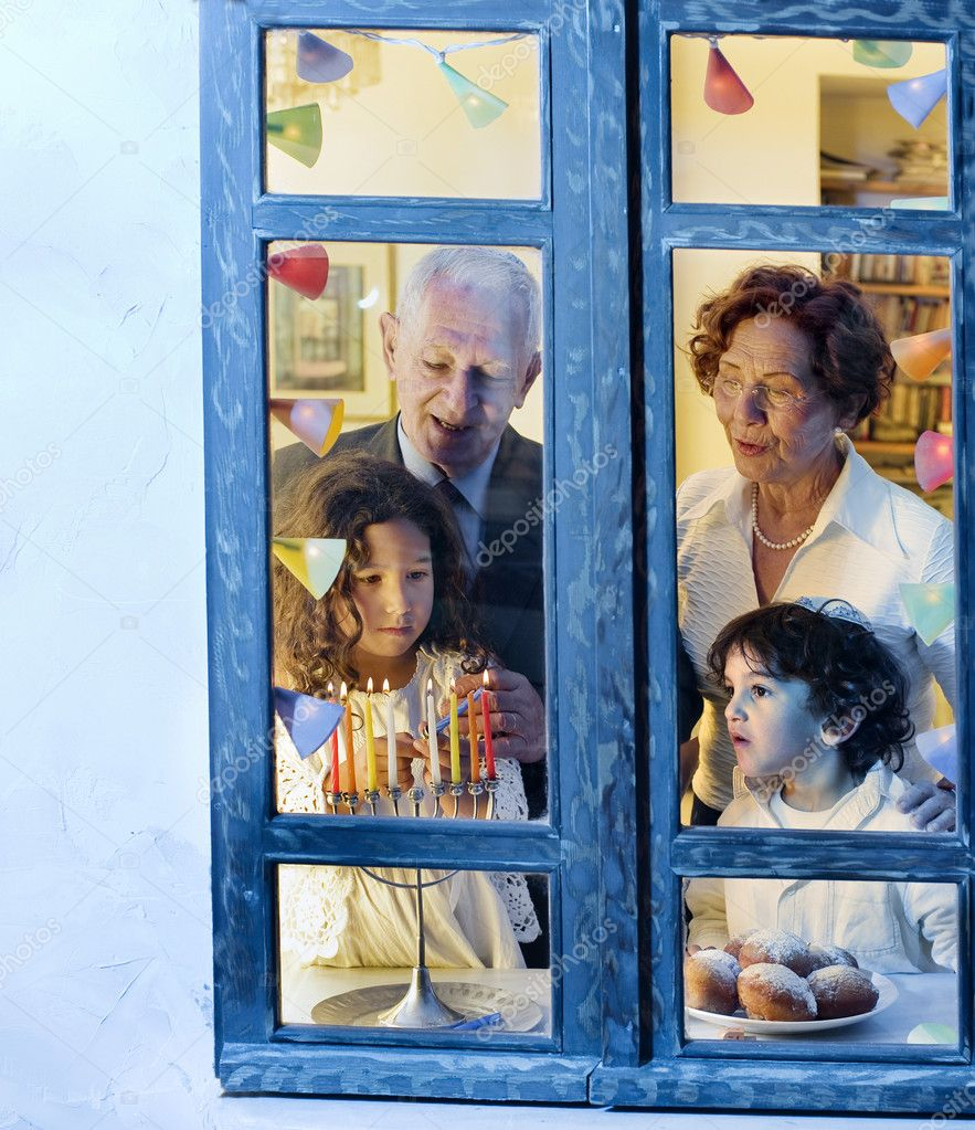 Grandparents and grandchildren with hannukkia, at the window — Stock Photo #1336072