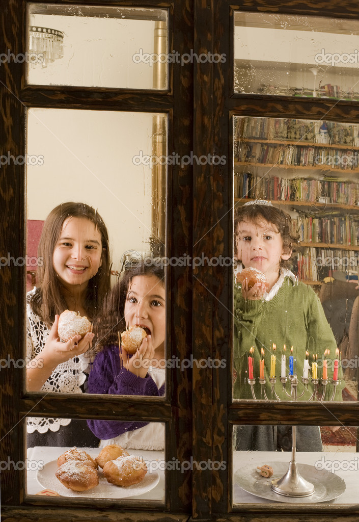 Children behind a rainy window in front of a Hanukkia eating traditional jelly doughnut in Hanukka  Stock Photo #1336938