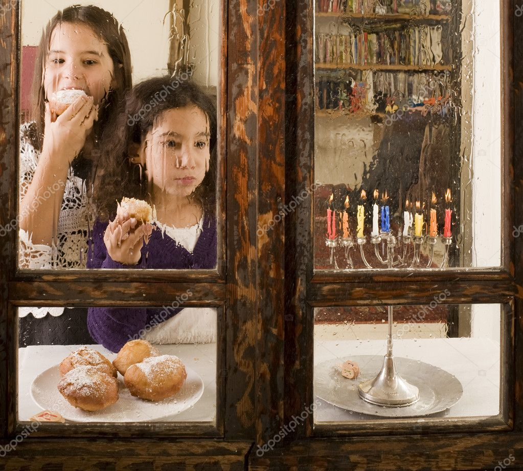 Children in front of a Hanukkia eating traditional jelly doughnut in Hanukka — Stock Photo #1336944
