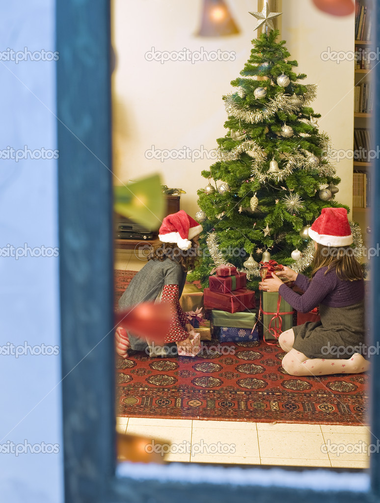 Two little girls opening chrismas presents watched from a snowy window — Stock Photo #1337216