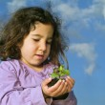 Girl holding plant — Stock Photo #1340858