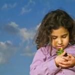Littel girl holding plant — Stock Photo #1340864