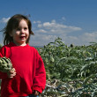 Young girl holding artichok — Stock Photo